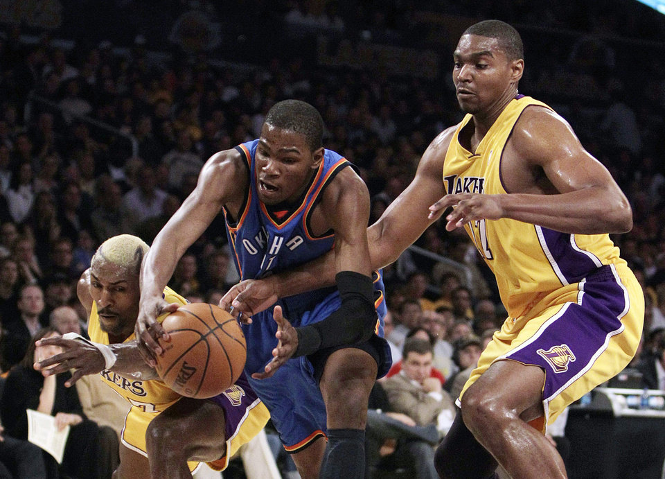Photo - Oklahoma City Thunder forward Kevin Durant, center, is pressured by Los Angeles Lakers' Ron Artest, left, and Andrew Bynum during the first half of Game 2 in a first-round NBA basketball playoff series in Los Angeles, Tuesday, April 20, 2010. (AP Photo/Jae C. Hong) ORG XMIT: LAS204