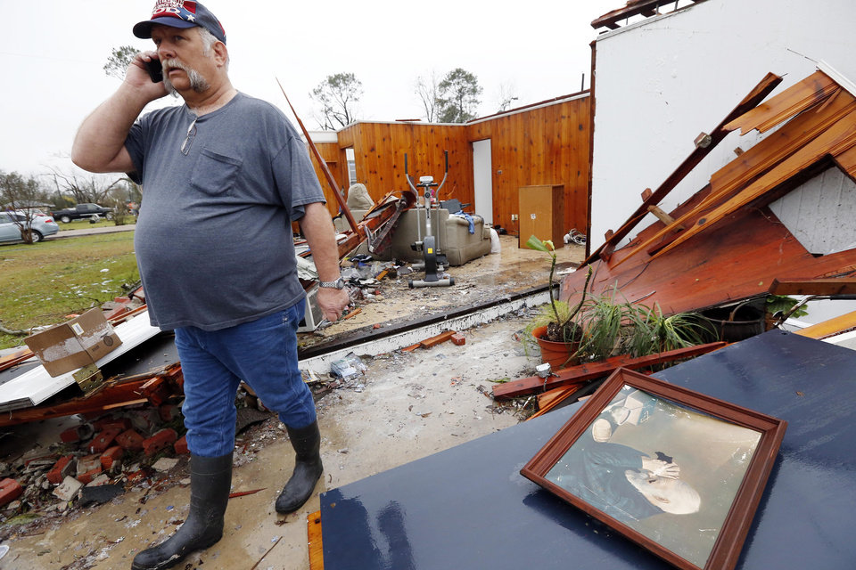Photo - David Dean walks past the water logged reproduction of a favorite painting of his late father in Petal, Miss., Tuesday, Feb. 12, 2013 following the Sunday afternoon tornado that caused damage throughout this community. Cleanup and salvage operations continued amid frequent rain storms. (AP Photo/Rogelio V. Solis)