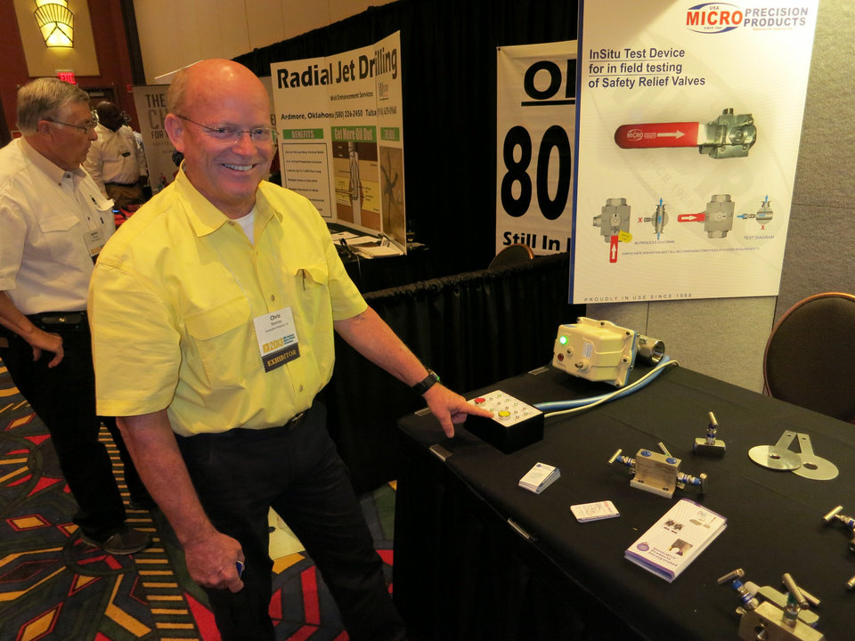 Photo - Chris Rooney demonstrates an Innovative Products Inc. pipeline valve mechanism designed to automaticlly close if it detects too much pressure. The demonstration is part of the Mid-Continent Digital Oilfield Conference in Tulsa. Photo by Adam Wilmoth, The Oklahoman