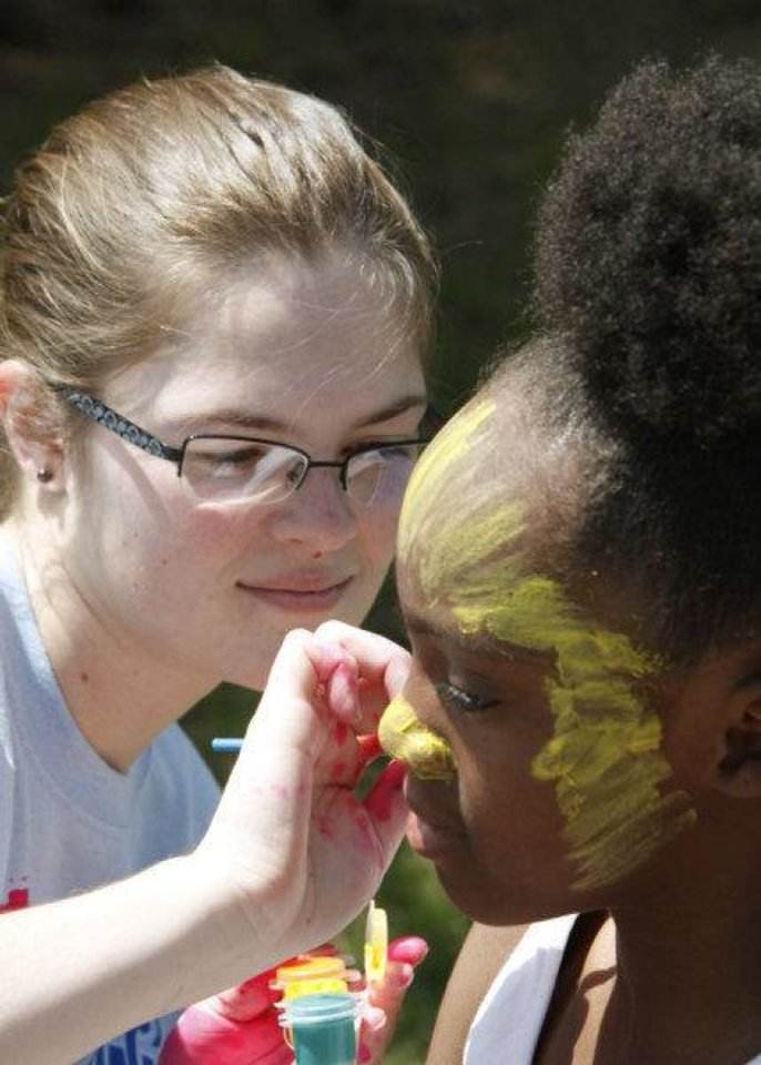 Photo - Hannah Craig paints the face of Tierra Williams, 9, during an Easter egg hunt and carnival Saturday at Plunkett Park at the University of Central Oklahoma in Edmond. Photo by Paul Hellstern, The Oklahoman  PAUL HELLSTERN