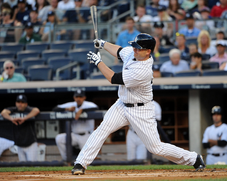 Photo - New York Yankees' Brian McCann follows through on an RBI double off of Cincinnati Reds starting pitcher Mike Leake in the first inning of an interleague baseball game at Yankee Stadium on Friday, July 18, 2014, in New York. (AP Photo/Kathy Kmonicek)