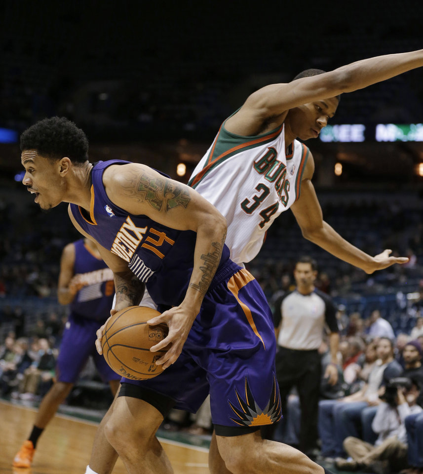 Photo - Phoenix Suns' Gerald Green (14) drives around Milwaukee Bucks' Giannis Antetokounmpo (34) during the first half of an NBA basketball game Wednesday, Jan. 29, 2014, in Milwaukee. (AP Photo/Jeffrey Phelps)