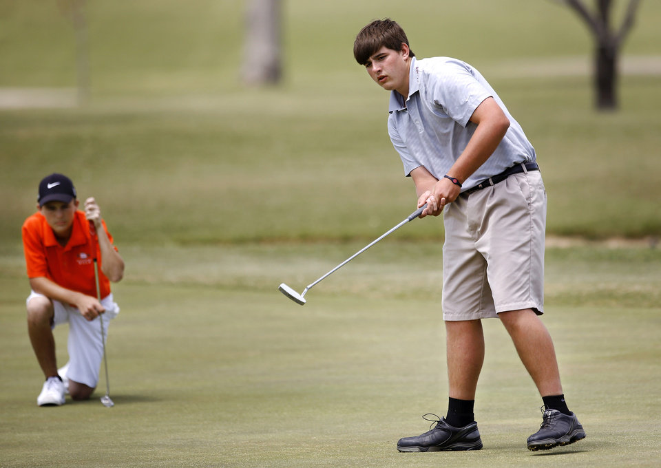 Photo - Quade Cummins of Weatherford sinks a putt on #18 to finish the round during Class 4A boy's state golf  tournament on Tuesday, May 7, 2013,  at  Hefner Golf Course in Oklahoma City.  AAt left is Nick Pierce of Sallisaw.  Photo  by Jim Beckel, The Oklahoman.