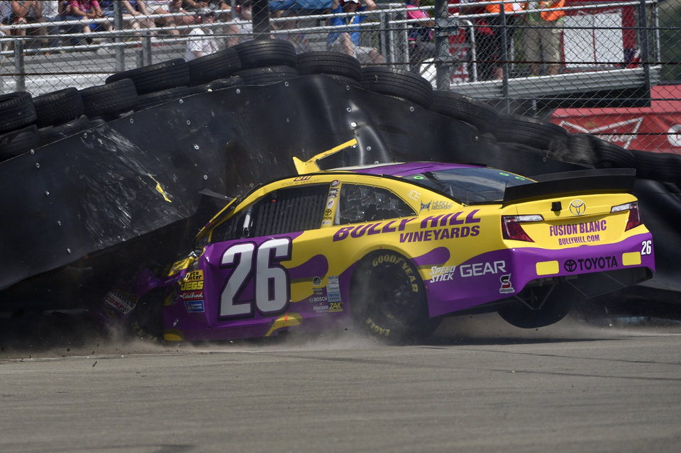 Photo - Cole Whitt (26) crashes into a tire wall off turn one during a NASCAR Sprint Cup Series auto race at Watkins Glen International, Sunday, Aug. 10, 2014, in Watkins Glen N.Y. (AP Photo/Derik Hamilton)