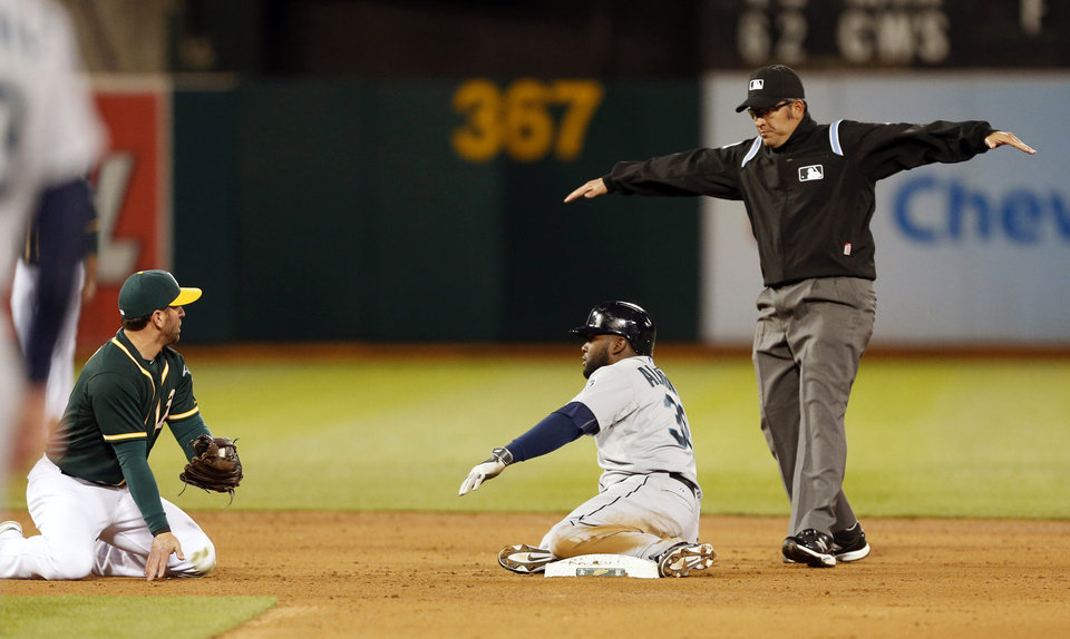 Photo - Seattle Mariners center fielder Abraham Almonte, center, is called safe by second base umpire Manny Gonzales as Oakland Athletics short stop Jed Lowrie, left, is near during the fifth inning of a baseball game, Thursday, April 3, 2014, in Oakland, Calif. (AP Photo/Beck Diefenbach)