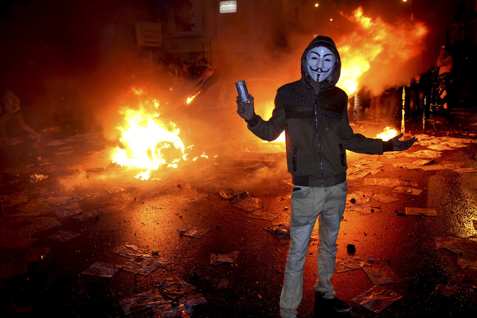 Photo - A masked protester poses with a tear gas canister in front of a burning vehicle during clashes between opponents of Egyptian President Mohammed Morsi and his Islamist supporters in Alexandria, Egypt, Friday, Dec. 21, 2012. Thousands of Islamists clashed with their opponents on Friday in Egypt's second largest city, Alexandria as the two sides hurled stones and youth protesters sat fire on vehicles belonging to Islamists, a day before the second leg of voting on a proposed constitution that has deeply polarized the nation.(AP Photo)
