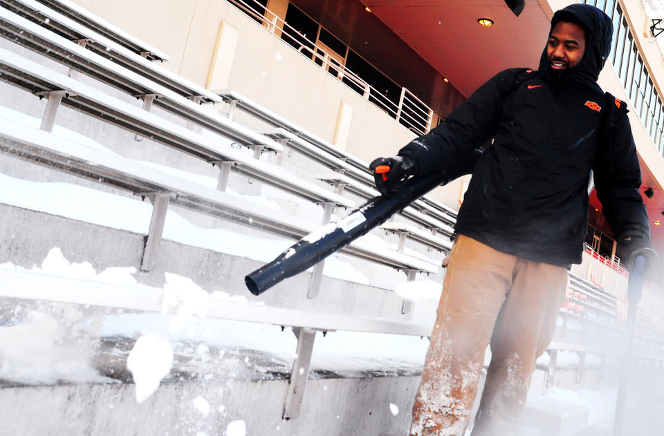 Photo - Garehtte Casper, 26 and an Oklahoma State student, walks rows of steps inside Boone Pickens Stadium with a snow blower on Friday to clear piles of snow collected after Stillwater and the campus of Oklahoma State received heavy snowfall on Thursday and Friday ahead of Saturday's bedlam football game. The Oklahoma State athletic department was forced to clear the snow quickly, using small tractors to clear the field on Dec. 6, 2013. KT King/For the Tulsa World