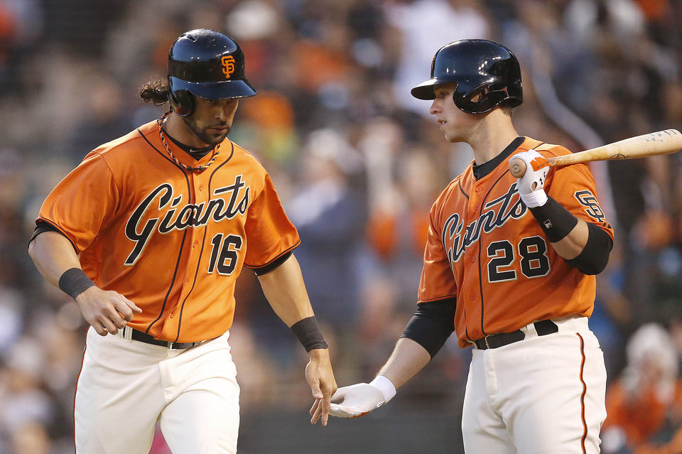 Photo - San Francisco Giants' Angel Pagan (16) is congratulated by Buster Posey (28) after scoring a run against the Minnesota Twins in the third inning of a baseball game Friday, May 23, 2014, in San Francisco. (AP Photo/Tony Avelar)