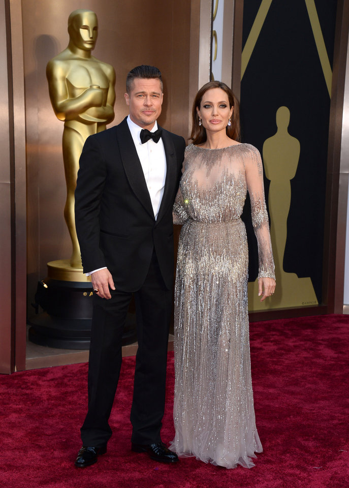 Photo - Brad Pitt, left, and Angelina Jolie arrive at the Oscars on Sunday, March 2, 2014, at the Dolby Theatre in Los Angeles.  (Photo by Jordan Strauss/Invision/AP)