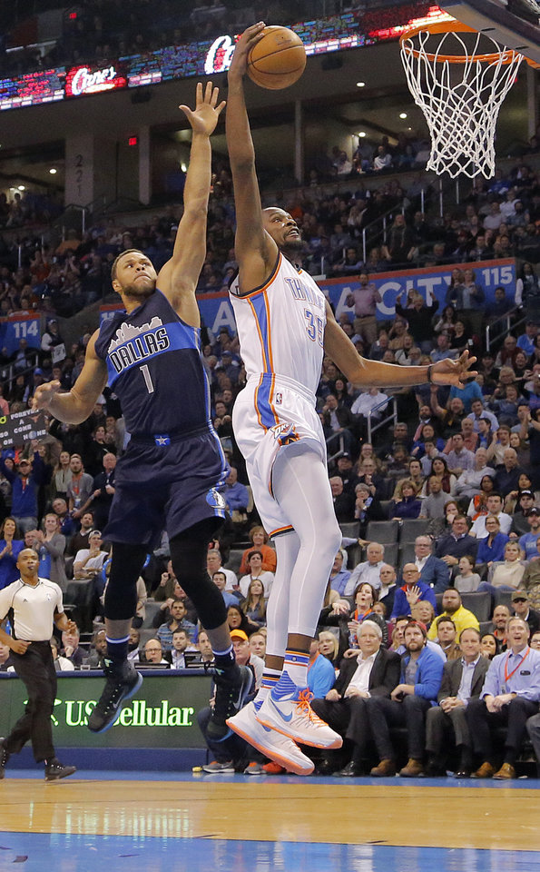 Photo - Oklahoma City's Kevin Durant (35) dunks the ball past Dallas' Justin Anderson (1) during the NBA basketball game between the Oklahoma City Thunder and the Dallas Mavericks at Chesapeake Energy Arena on Wednesday, Jan. 13, 2016, in Oklahoma City, Okla.  Photo by Chris Landsberger, The Oklahoman