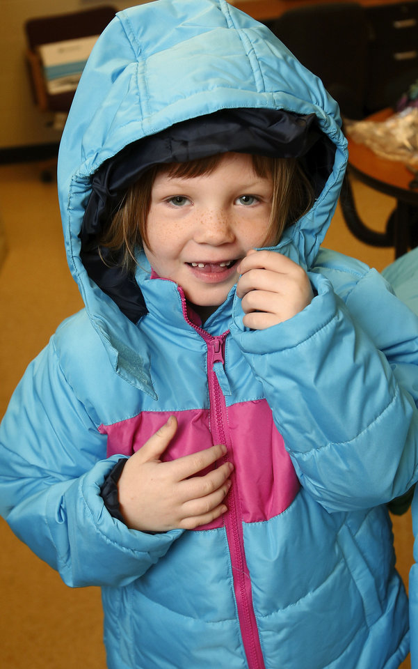 Photo - Kindergartener Summer Beagle tries on her new coat Monday afternoon at Southern Hills Elementary. About 2,000 children in Oklahoma City Public Schools will receive new coats from a national nonprofit called Operation Warm.  Jim Beckel - THE OKLAHOMAN