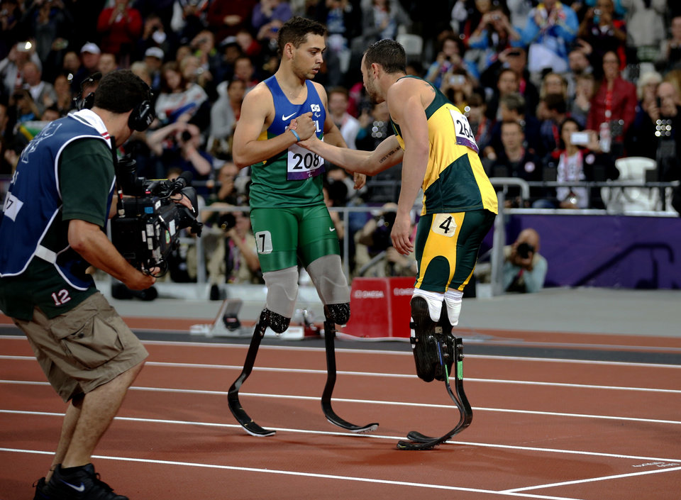 Photo -   Gold medal winner Brazil's Alan Fonteles Cardoso Oliveira, left, embraces silver medalist south Africa's Oscar Pistorius after they ran the men's 200m T44 category final during the athletics competition at the 2012 Paralympics, Sunday, Sept. 2, 2012, in London. (AP Photo/Matt Dunham)