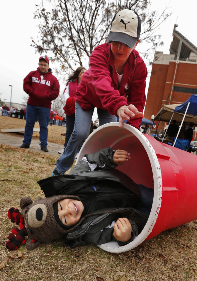 Photo - Fans pass the time in unusuall ways before a Bedlam college football game between the University of Oklahoma Sooners (OU) and the Oklahoma State Cowboys (OSU) at Gaylord Family-Oklahoma Memorial Stadium in Norman, Okla., on Saturday, Dec. 6, 2014. Brody Brown, 4, gets a ride in barrells used for a toss game by his mother Brandi Hokit.  Photo by Steve Sisney, The Oklahoman