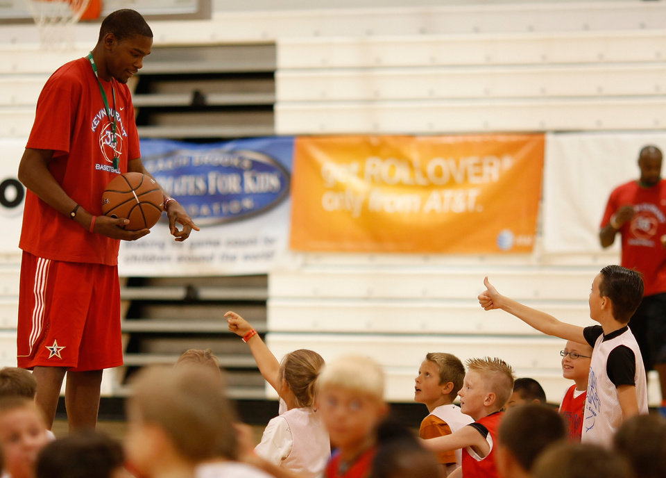 Photo - Basketball camp participants help line Kevin Durant up for a behind the back half-court shot. Kevin Durant held a basketball camp Wednesday, June 30, 2010, at Heritage Hall in Oklahoma City. Photo by Mitchell Alcala, The Oklahoman.