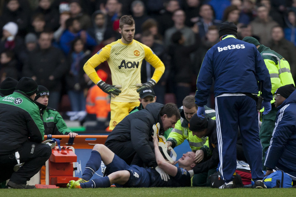 Photo - Manchester United's Phil Jones, bottom, is treated on the pitch before being carried off injured during his team's English Premier League soccer match against Stoke at the Britannia Stadium, Stoke, England, Saturday Feb. 1, 2014. (AP Photo/Jon Super)