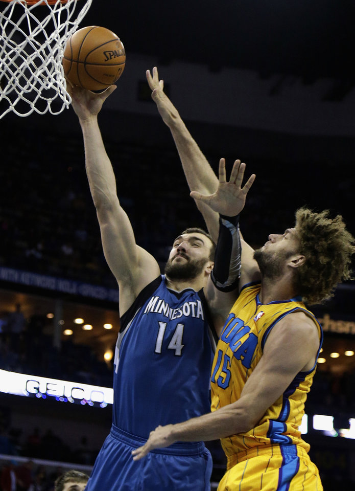 Photo - Minnesota Timberwolves center Nikola Pekovic (14) goes to the basket around New Orleans Hornets forward Ryan Anderson (33) during the first half of an NBA basketball game in New Orleans, Friday, Jan. 11, 2013. (AP Photo/Bill Haber)