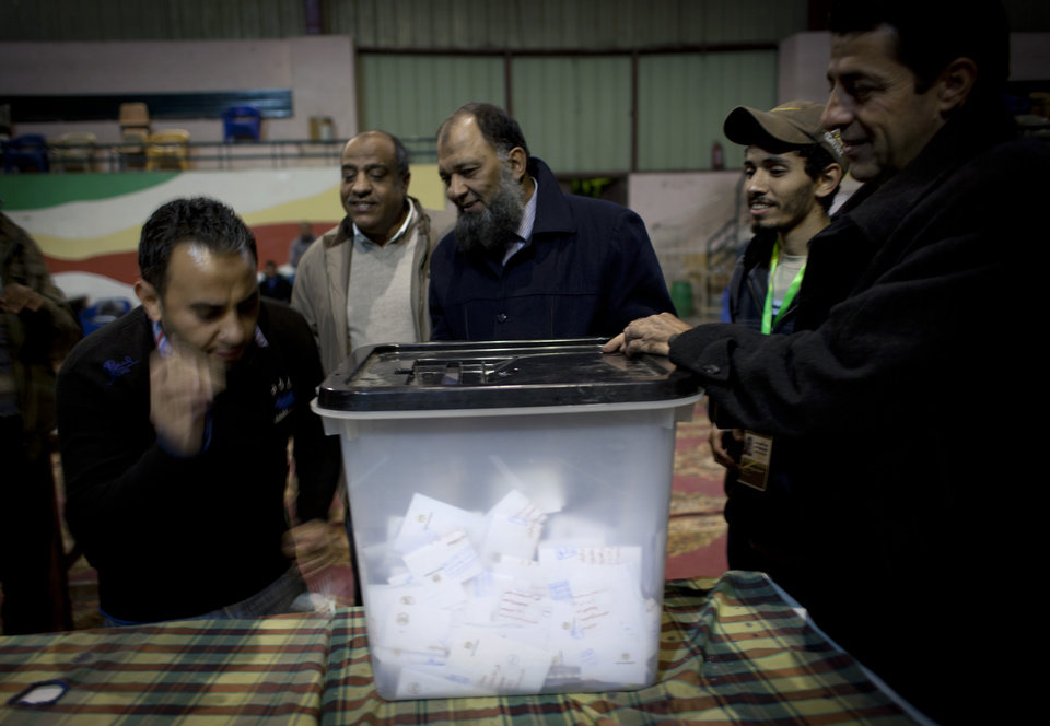 Photo - Egyptian election workers unseal a ballot box for counting at the end of the second round of a referendum on a disputed constitution drafted by Islamist supporters of president Mohammed Morsi at a polling station in Giza, Egypt, Saturday, Dec. 22, 2012. Egypt's Islamist-backed constitution headed toward likely approval in a final round of voting on Saturday, but the deep divisions it has opened up threaten to fuel continued turmoil. (AP Photo/Nasser Nasser)