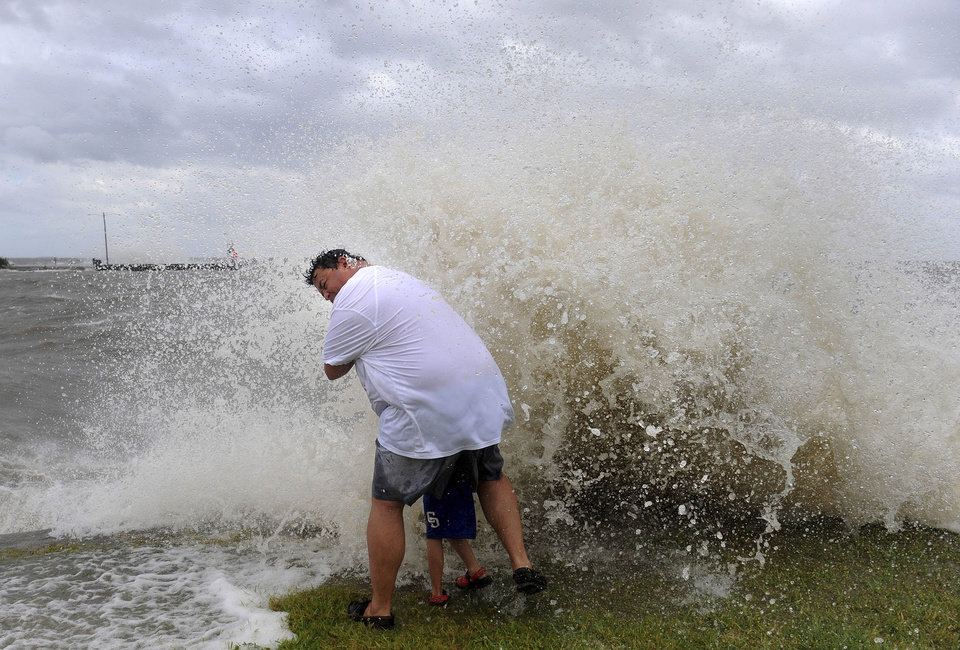 Photo -   Douglas Silva holds his son, Bence, 5, as they are swamped by wind pushed waves on the sea wall of Lake Pontchartrain Tuesday Aug. 28, 2012, as Hurricane Isaac starts to take effect in New Orleans. The storm was arriving at the seventh anniversary of Hurricane Katrina, which devastated Louisiana and Mississippi when it struck on Aug. 29, 2005. (AP Photo/The Advocate, Arthur D. Lauck) MAGS OUT; INTERNET OUT; NO SALES; TV OUT; NO FORNS; LOUISIANA BUSINESS INC. OUT (INCLUDING GREATER BATON ROUGE BUSINESS REPORT, 225, 10/12, INREGISTER, LBI CUSTOM)