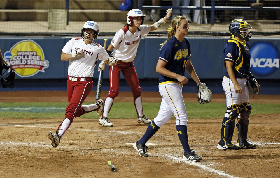 Photo - OU's Erica Sampson (63) scores in front of teammate Brianna Turang (2) near Michigan pitcher Sara Driesenga (10) and catcher Lauren Sweet (25) in the fifth inning during an NCAA softball game in the Women's College World Series between Oklahoma and Michigan at ASA Hall of Fame Stadium, Thursday, May 30, 2013. OU won, 7-1. Photo by Nate Billings, The Oklahoman