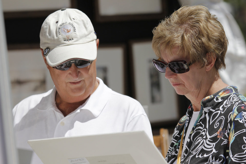 Photo - Peter and June Wipfli look at prints from artist Michael Bond during opening day of the Festival of the Arts in downtown Oklahoma City TUesday, April 24, 2012. Photo by Doug Hoke, The Oklahoman