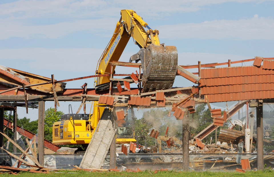 Photo -  A track hoe is used to tear down the former Jackie Cooper dealership at 9601 N May Ave. in The Village on Wednesday. Photo by Paul B. Southerland, The Oklahoman   PAUL B. SOUTHERLAND -  PAUL B. SOUTHERLAND