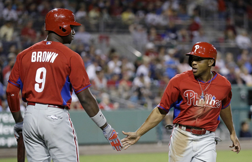 Photo - Philadelphia Phillies' Ben Revere, right, is greeted by teammate Domonic Brown (9) after scoring on an RBI-single hit by Marlon Byrd in the fifth inning of an exhibition spring baseball game against the Boston Red Sox in Fort Myers, Fla., Saturday, March 15, 2014. (AP Photo/Gerald Herbert)