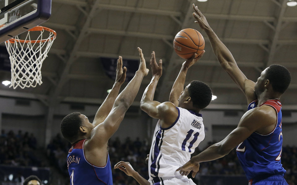 Photo - TCU forward Brandon Parrish (11) attempts a shot as Kansas' Wayne Selden Jr. (1) and Andrew Wiggins (22) defend in the second half of an NCAA college basketball game, Saturday, Jan. 25, 2014, in Fort Worth, Texas. Kansas won 91-69. (AP Photo/Brandon Wade)