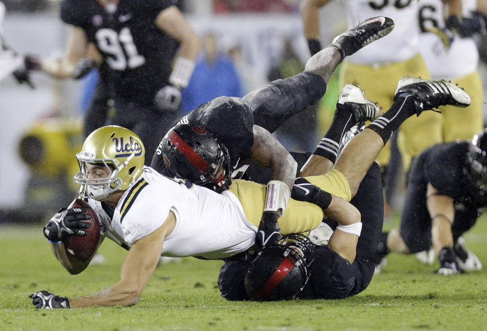 Photo - UCLA tight end Joseph Fauria is brought down after a reception against Stanford during the first half of the Pac-12 championship NCAA college football game in Stanford, Calif., Friday, Nov. 30, 2012. (AP Photo/Marcio Jose Sanchez)