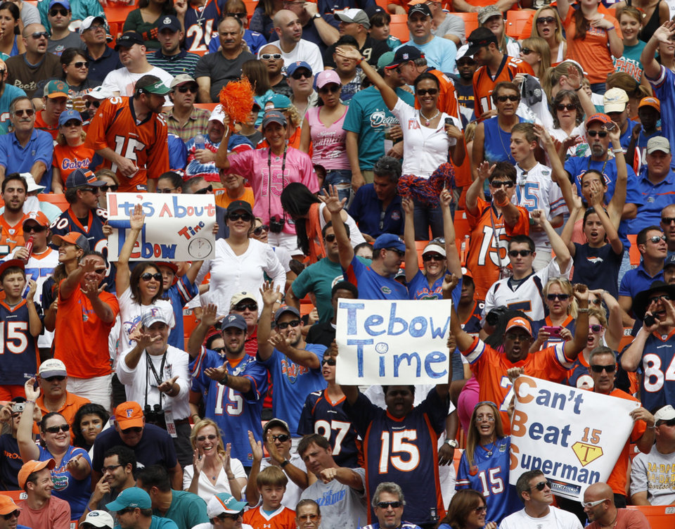 Photo -   Fans cheer as Denver Broncos quarterback Tim Tebow walks onto the field during the first half of the Broncos' NFL football game against the Miami Dolphins, Sunday, Oct. 23, 2011, in Miami. (AP Photo/Hans Deryk)