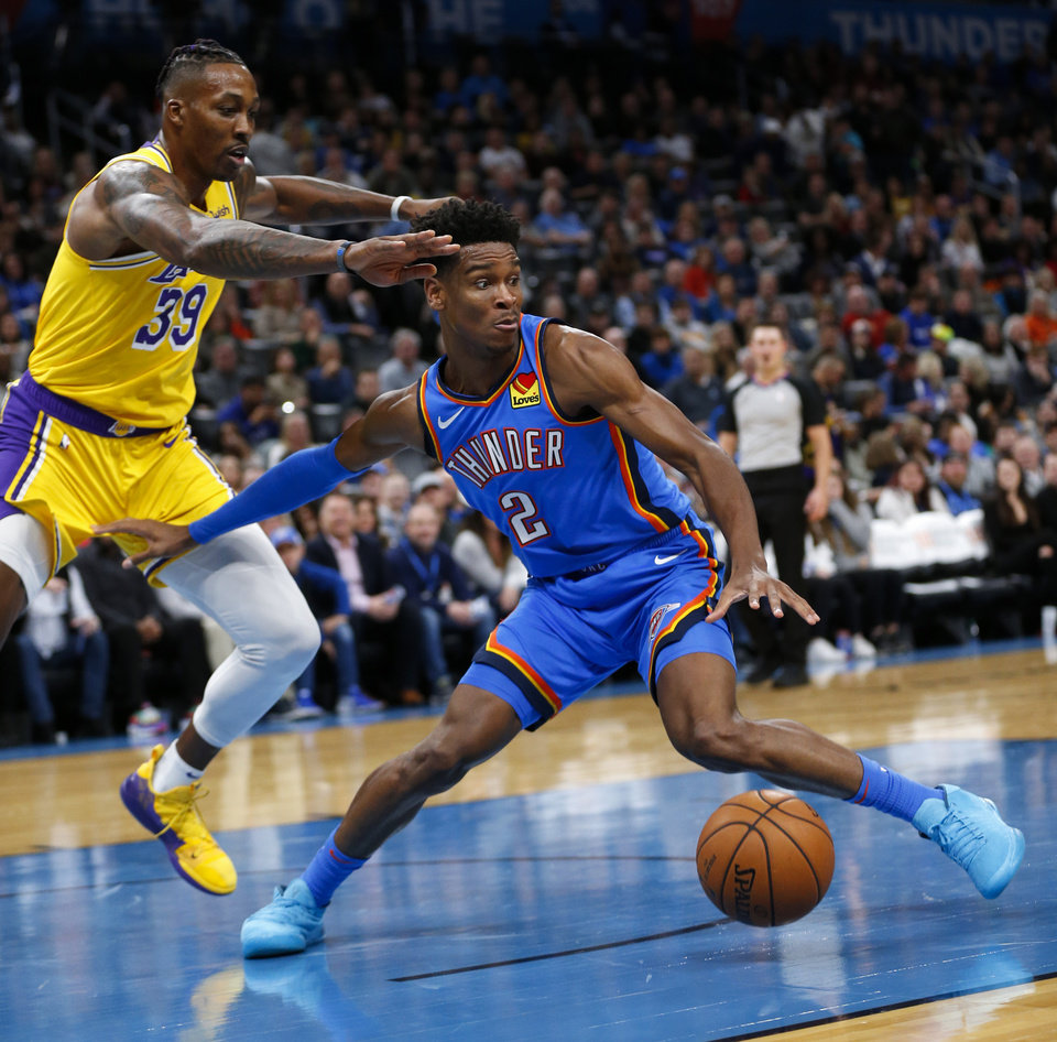 Photo - Oklahoma City's Shai Gilgeous-Alexander (2) spins away from Los Angeles' Dwight Howard (39) before making a shot in the second quarter during an NBA basketball game between the Oklahoma City Thunder and the Los Angeles Lakers at Chesapeake Energy Arena in Oklahoma City, Friday, Nov. 22, 2019. [Nate Billings/The Oklahoman]