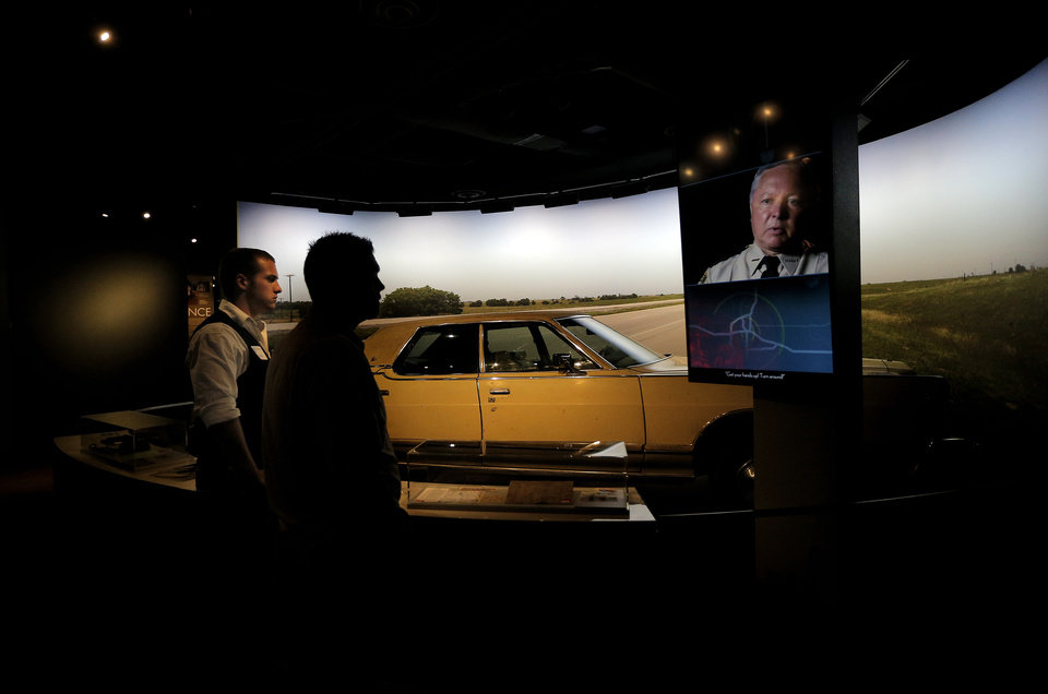 Photo -  Colton Craft, left, and John Craft watch a video about the arrest of Timothy McVeigh. His 1977 Mercury Grand Marquis sits on display in the background at in the newly renovated second floor of The Oklahoma City National Memorial & Museum, Sunday, Sept. 14, 2014. Photo by Sarah Phipps, The Oklahoman   SARAH PHIPPS -  SARAH PHIPPS