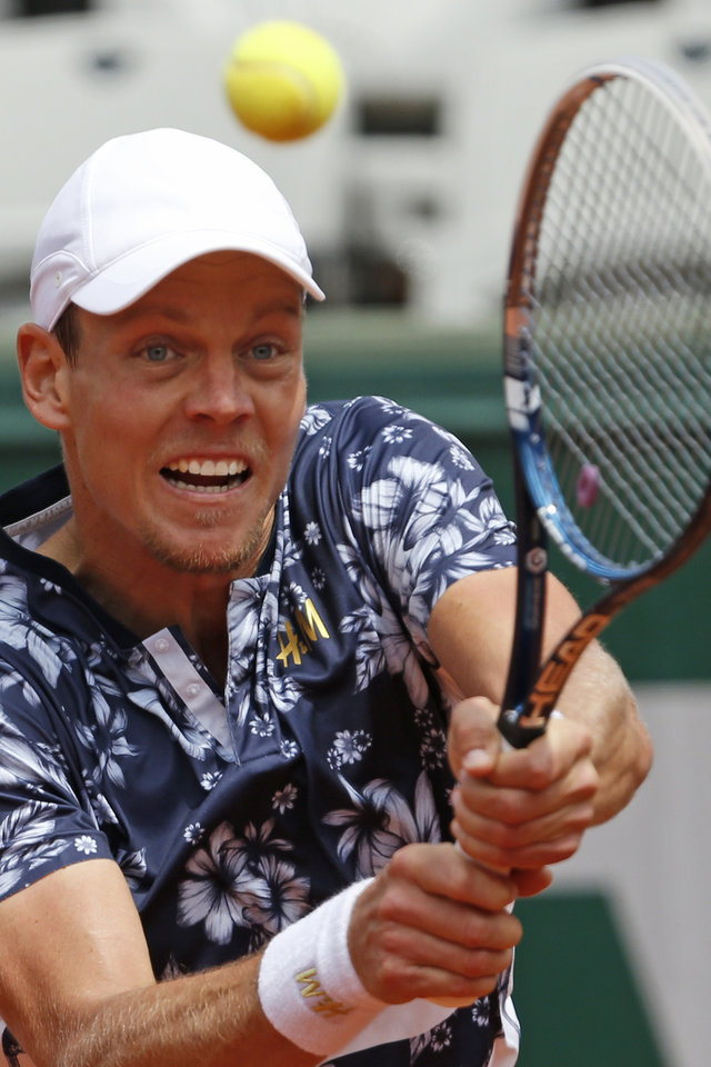 Photo - Tomas Berdych of the Czech Republic returns the ball during the fourth round match of the French Open tennis tournament against John Isner of the U.S. at the Roland Garros stadium, in Paris, France, Sunday, June 1, 2014. Berdych won in three sets 6-4, 6-4, 6-4. (AP Photo/Darko Vojinovic)