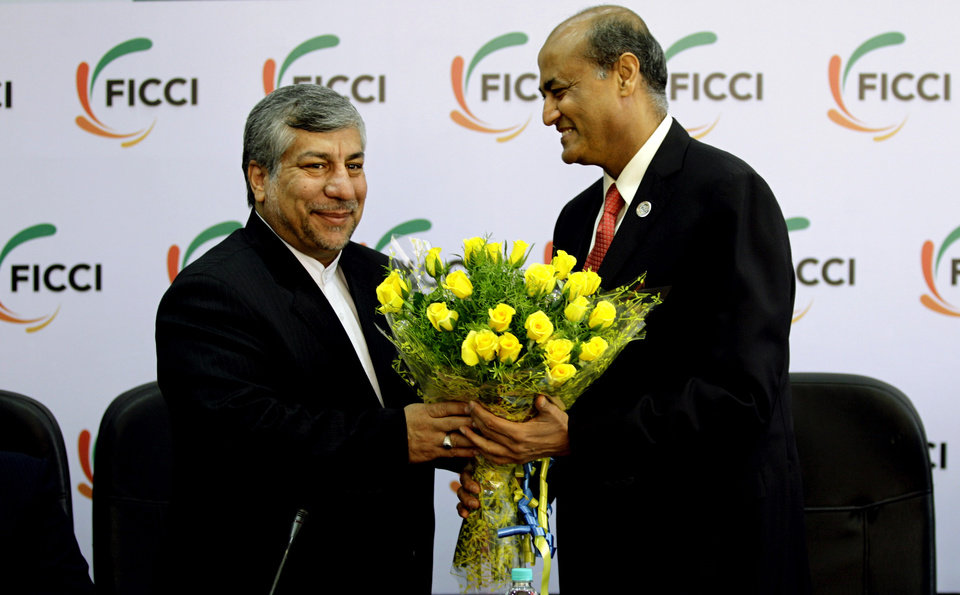 Photo -   Federation of Indian Chambers of Commerce and Industry President, R. V. Kanoria, right, greets Iranian Energy Minister Majid Namjoo with a bouquet of flowers before an interactive business meeting with FICCI members in New Delhi, India, Wednesday, Oct. 10, 2012. (AP Photo/Altaf Qadri)