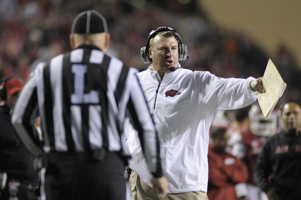 Photo - FILE - In this Nov. 2, 2013, file photo, Arkansas coach Bret Bielema talks to an official in the second half of an NCAA college football game in Fayetteville, Ark. The NCAA's switch to a 40-second play clock in 2008 altered the way college football games were managed, the pace of play no longer in the hands of the officials but the two teams' offenses. With defenses struggling to keep up, the NCAA football rules committee earlier this year looked at possibly prohibiting teams from snapping the ball until at least 10 seconds had run off the 40-second play clock. Supporters of the rule, like Arkansas' Bret Bielema and Alabama's Nick Saban, argued it was needed to allow teams to substitute for fatigued players and prevent injuries. (AP Photo/Beth Hall, File)