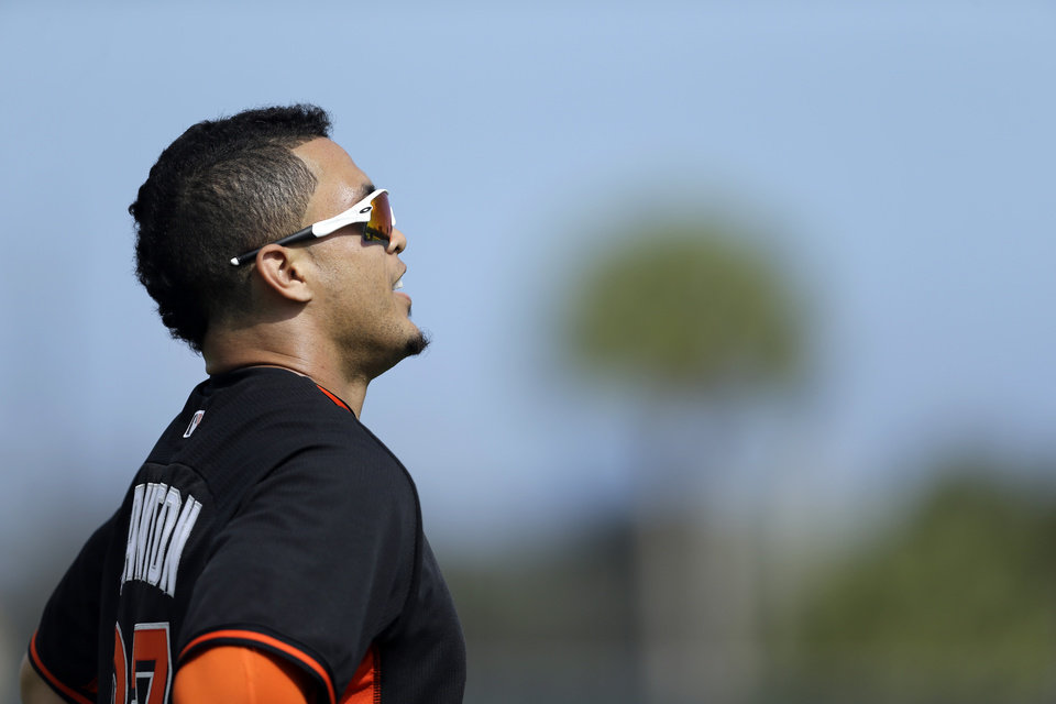 Photo - Miami Marlins' Giancarlo Stanton pauses after running sprints with his teammates during spring training baseball practice, Thursday, Feb. 20, 2014, in Jupiter, Fla. (AP Photo/Jeff Roberson)