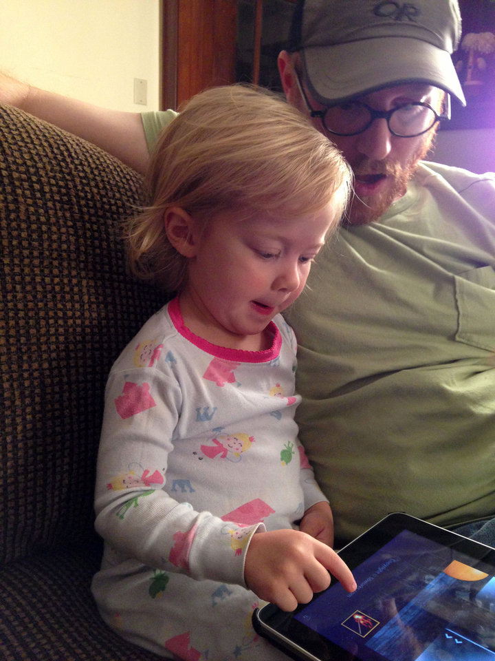 Photo - In this December 2012 image provided by Brandi Koskie, her husband Shelton Koskie is shown seated with their daughter Paisley Koskie, then age two, at their Wichita, Kansas home as she plays with an iPad. An increasing number of parents of toddlers are finding their tech-savvy 2- and 3-year-old kids are obsessed with selfies. (AP Photo/Brandi Koskie)