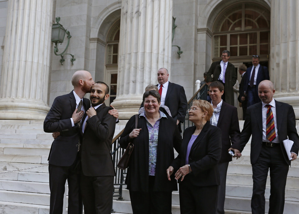 Photo - Plaintiffs and gay rights activists Derek Kitchen, left, and his partner Moudi Sbeity embrace as they leave court with other gay rights supporters after a hearing at the U.S. Circuit Court of Appeals in Denver, Thursday, April 10, 2014. The court is to decide if it agrees with a federal judge in Utah who in mid-December overturned a 2004 voter-passed gay marriage ban, saying it violates gay and lesbian couples' rights to due process and equal protection under the 14th Amendment. (AP Photo/Brennan Linsley)