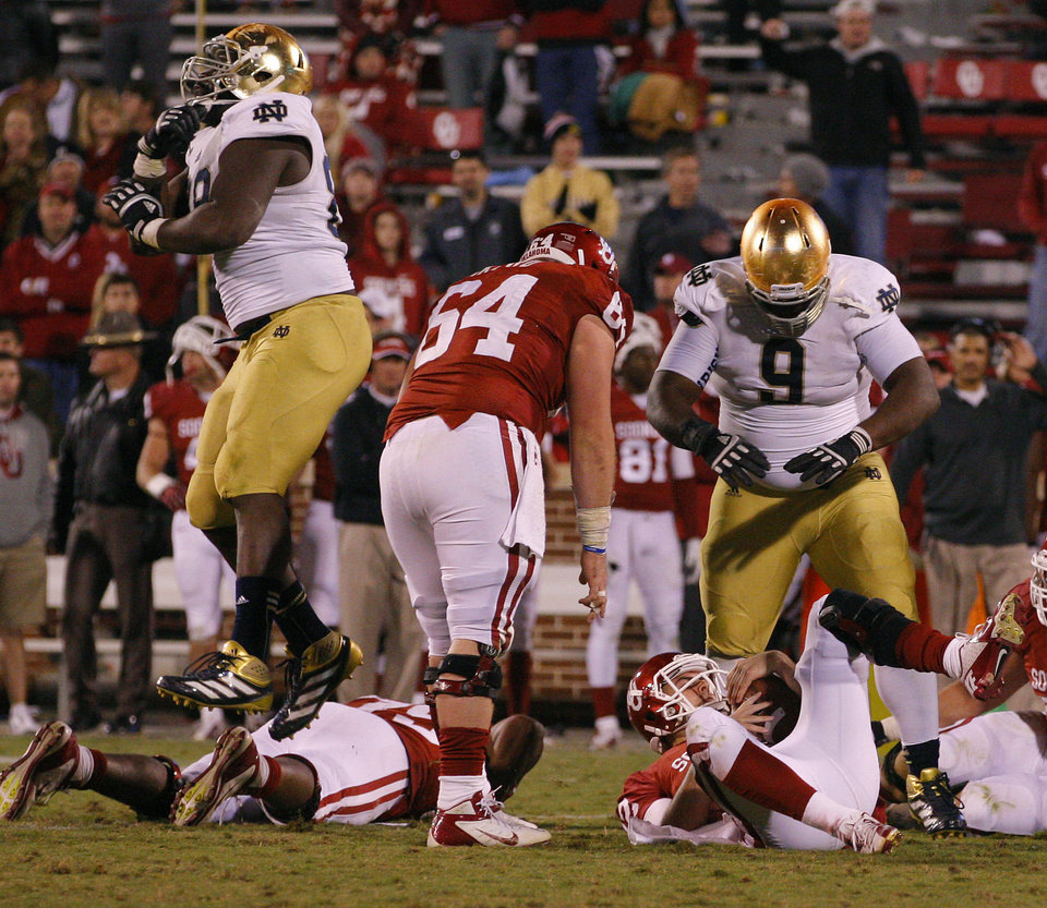 Photo - CELEBRATION: Notre Dame's Kapron Lewis-Moore (89) , left, and Louis Nix III (9) celebrate over OU's Landry Jones (12) after the last play of the game during the college football game between the University of Oklahoma Sooners (OU) and the Notre Dame Fighting Irish at Gaylord Family-Oklahoma Memorial Stadium in Norman, Okla., Saturday, Oct. 27, 2012. Oklahoma lost 30-13. Photo by Bryan Terry, The Oklahoman
