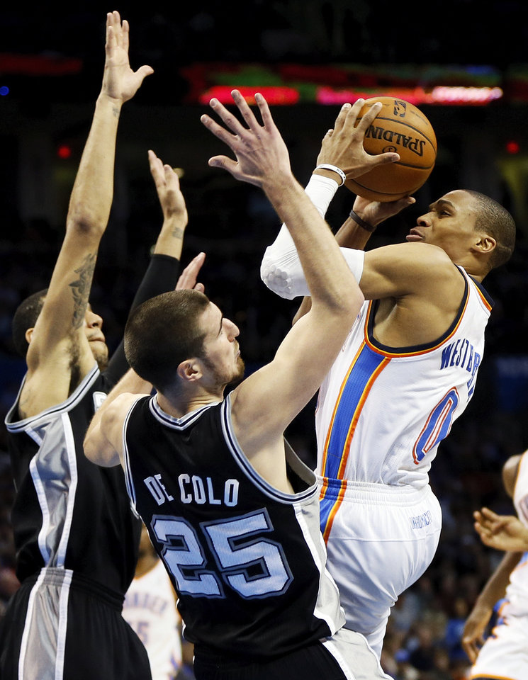 Oklahoma City\'s Russell Westbrook (0) moves to the hoop against San Antonio\'s Nando de Colo (25) and Danny Green (4) during an NBA basketball game between the Oklahoma City Thunder and the San Antonio Spurs at Chesapeake Energy Arena in Oklahoma City, Thursday, April 4, 2013. The Thunder won 100-88. Photo by Nate Billings, The Oklahoman