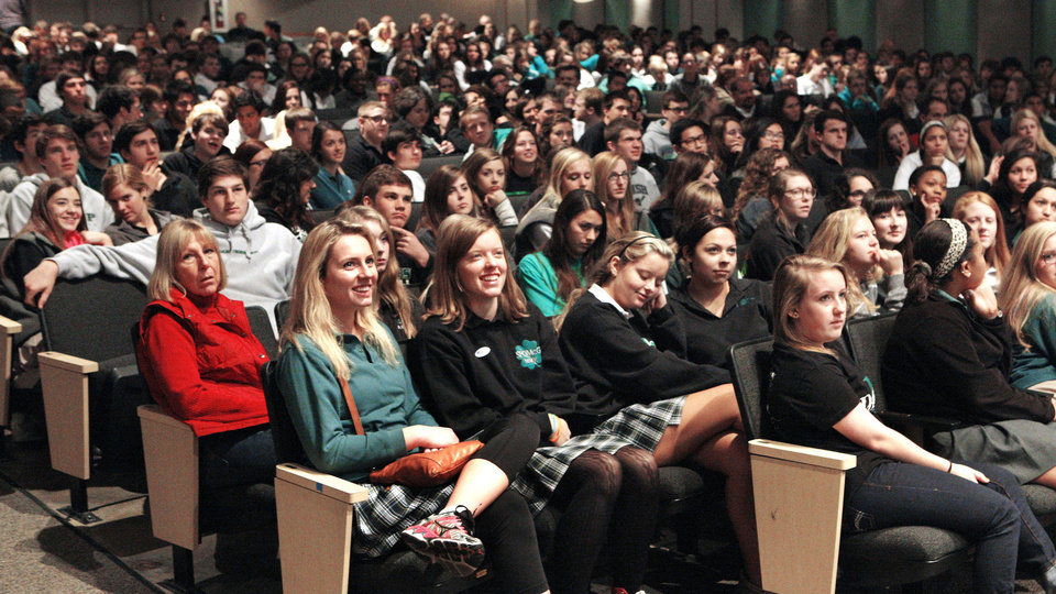 Photo - Students listen Wednesday as Cardinal Roger Mahony gives a presentation about immigration at Bishop McGuinness High School in Oklahoma City.