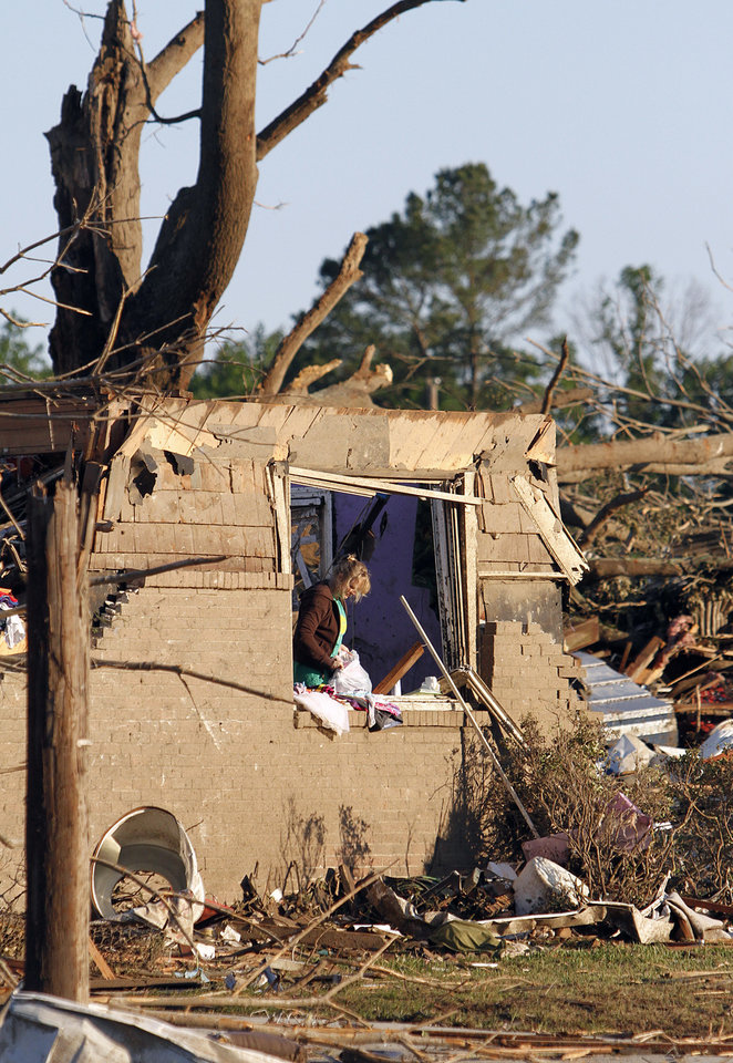 Photo - Vicki Wood searches through what is left of her daughter's home Thursday, April 28, 2011 after a tornado hit Pleasant Grove just west of downtown Birmingham, Ala., Wednesday afternoon. (AP Photo/Butch Dill)