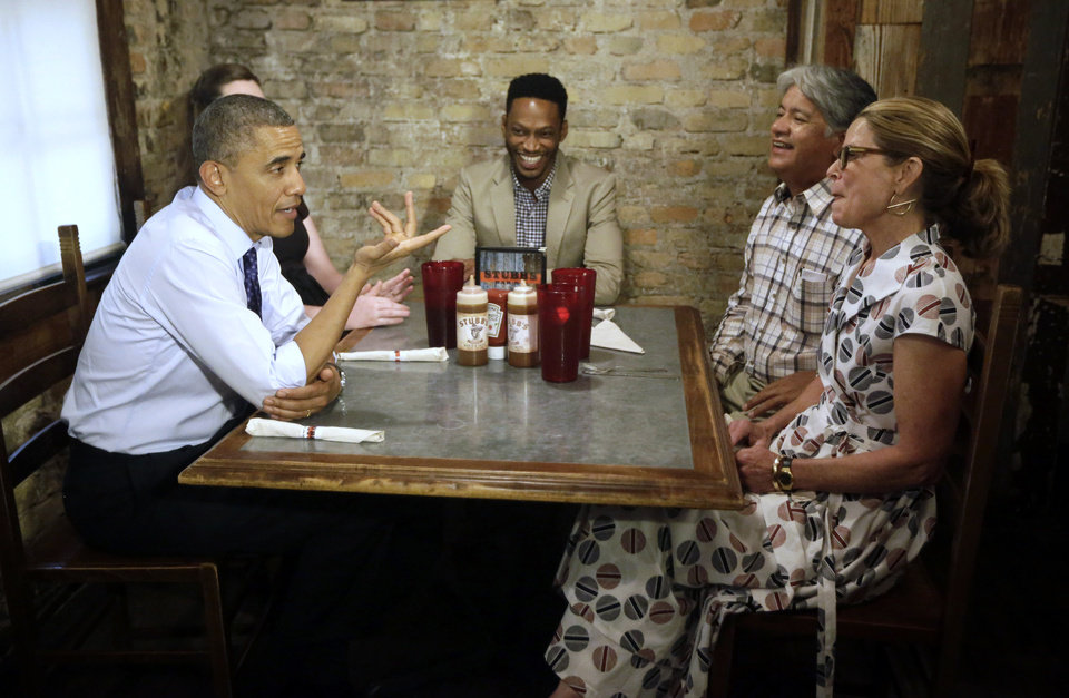 Photo - President Barack Obama, left, stops to meets local Austin residence at Stubb's Bar-B-Q restaurant, Thursday, May 9, 2013 in Austin, Texas. Sitting with Obama are from left to right, Caroline Sweet, Tyson Simmons, Joe Alonzo, and Agnes Wommack. (AP Photo/Pablo Martinez Monsivais)