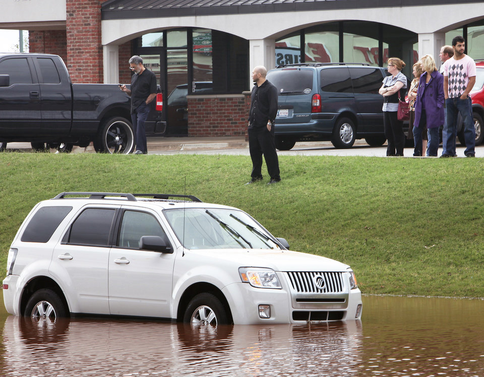 Photo - Victims of the high water and others look over the flooded vehicles Monday on Pennsylvania Avenue just south of Memorial Road.  PHOTO BY DAVID MCDANIEL, THE OKLAHOMAN