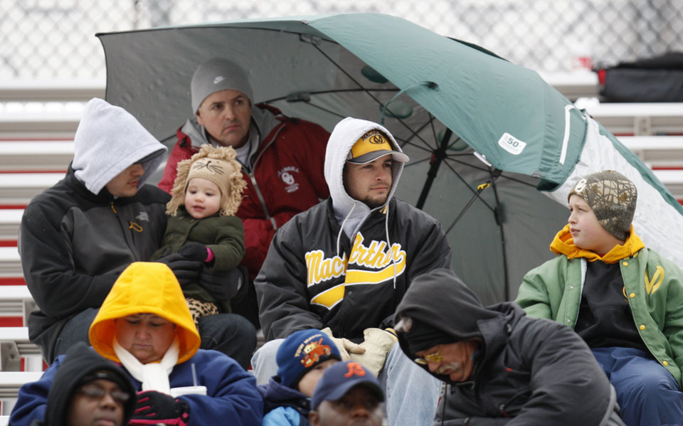 Photo - Lawton MacArthur fans are bundled up as they watch a high school football playoff Class 5A semifinal game between Lawton MacArthur and Ardmore in Yukon, Okla., Saturday, Nov. 26, 2011. Photo by Nate Billings, The Oklahoman