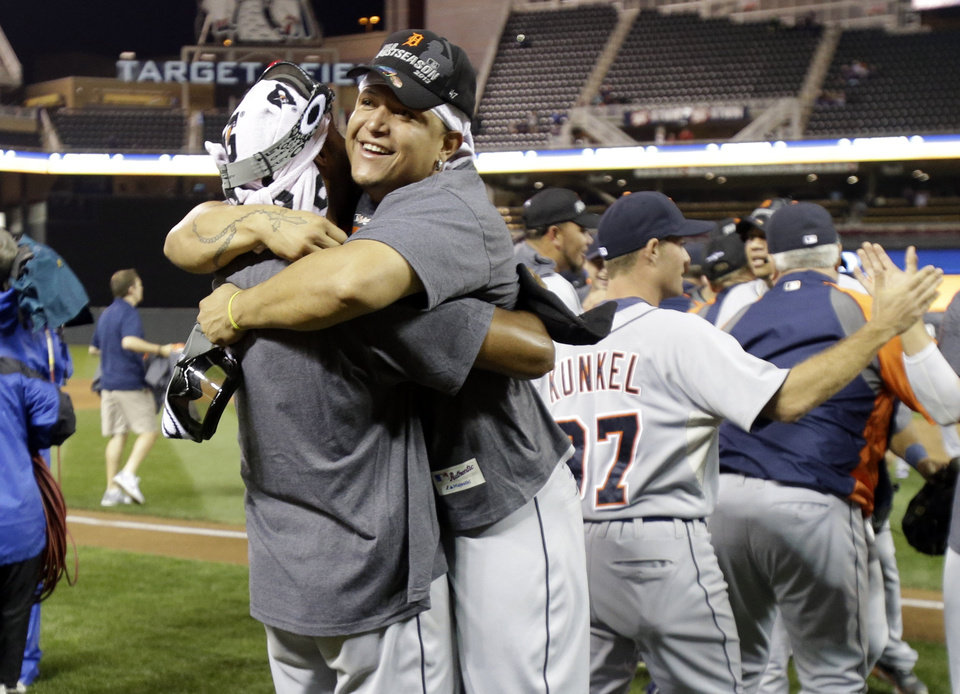 Photo - Detroit Tigers' Miguel Cabrera, right, gets a hug  on the field after the Tigers won the American League Central Division title after beating the Minnesota Twins 1-0 in a baseball game, Wednesday, Sept. 25, 2013, in Minneapolis. (AP Photo/Jim Mone)