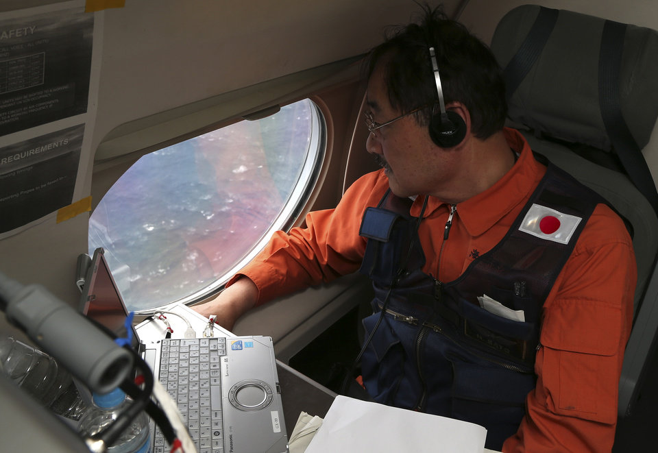 Photo - Communications specialist Hidetaka Sato on a Japan Coast Guard Gulfstream aircraft, looks out of a window searching for the missing Malaysia Airlines Flight MH370 in Southern Indian Ocean, near Australia, Tuesday, April 1, 2014. Bad weather and poor visibility caused the search to be called off early with the coast guard plane only completing one of its three 210 nautical mile legs. (AP Photo/Rob Griffith, Pool)