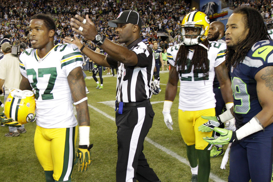 Photo -   An official gestures as Green Bay Packers cornerback Sam Shields (37), safety Jerron McMillian (22) and Seattle Seahawks free safety Earl Thomas (29) leave the field in the second half of an NFL football game, Monday, Sept. 24, 2012, in Seattle. After a period of confusion, a Seahawks touchdown by wide receiver Golden Tate was allowed to stand for the 14-12 win. (AP Photo/Ted S. Warren)