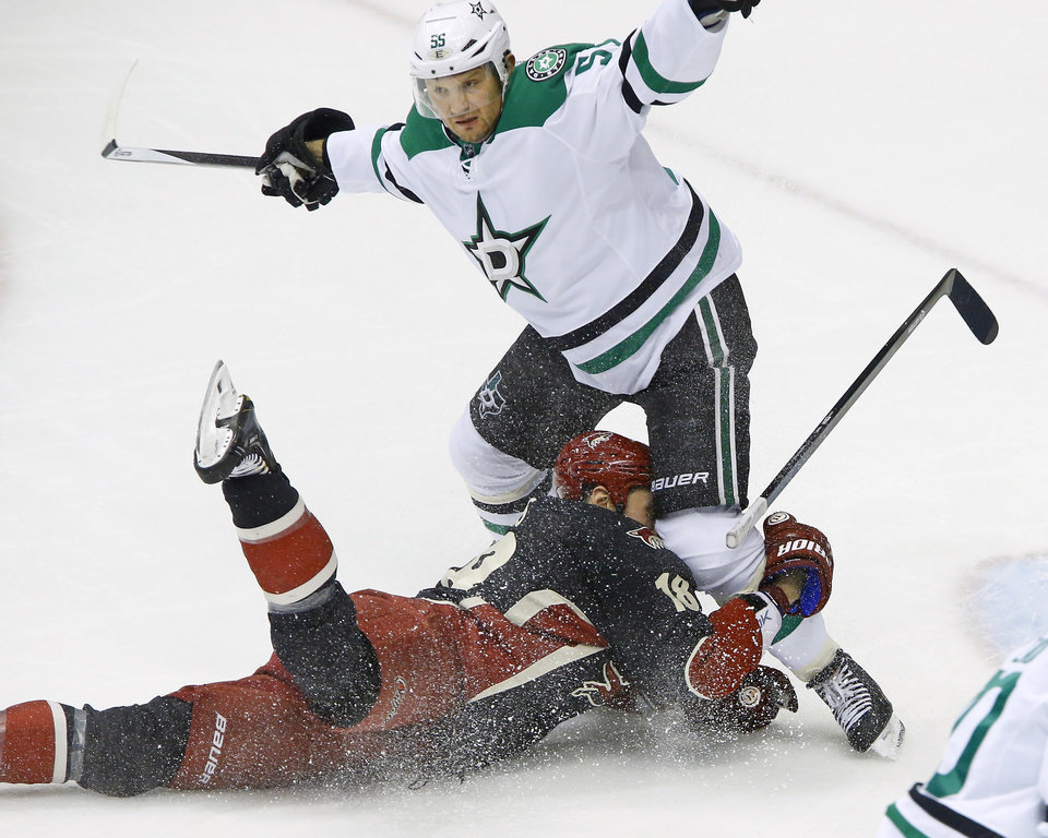 Photo - Phoenix Coyotes right wing David Moss (18) is pulled down by Dallas Stars defenseman Sergei Gonchar (55) during the second period of their NHL hockey game, Tuesday, Feb. 4, 2014 in Glendale, Ariz. (AP Photo/The Arizona Republic, David Kadlubowski)