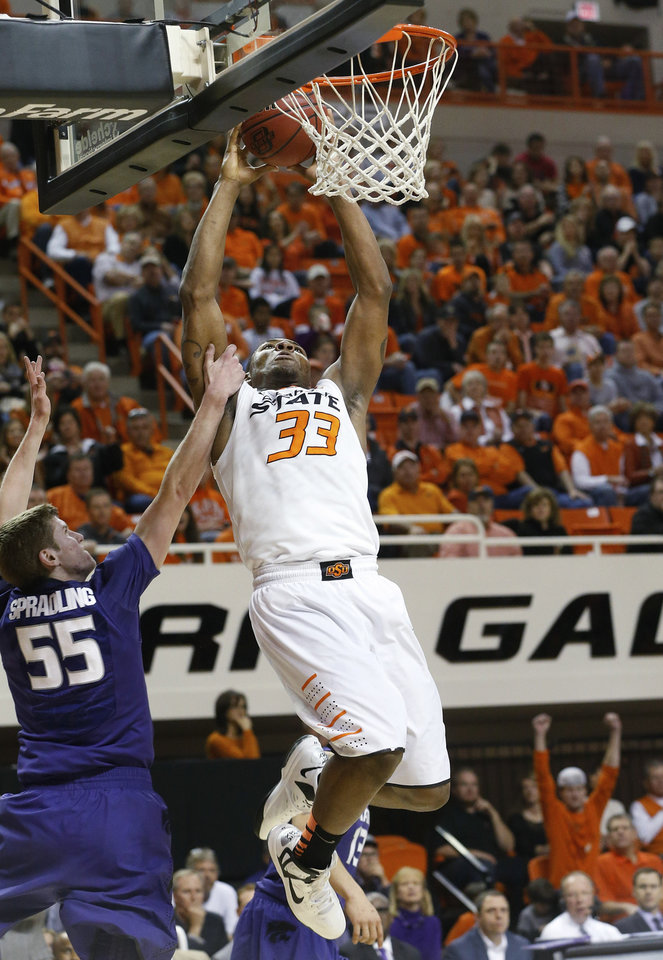 Photo - Oklahoma State guard Marcus Smart (33) is fouled by Kansas State guard Will Spradling (55) during the first half of an NCAA college basketball game in Stillwater, Okla., Saturday, March 9, 2013. (AP Photo/Sue Ogrocki)