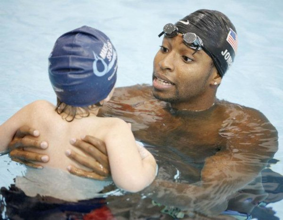 Olympic gold medalist Cullen Jones teaches children how to put their faces in the water Thursday at the Oklahoma City Community College pool. Jones is touring the country as part of the Make a Splash program, an anti-drowning intiative created by the USA Swimming Foundation. PAUL HELLSTERN - THE OKLAHOMAN